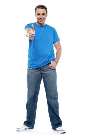 yup: Cheerful young man showing thumbs up isolated on white background Stock Photo