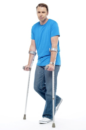 Painful expression by young man walking with help of crutches. Indoor studio shot photo