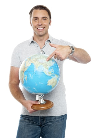 Isolated young man pointing at globe while holding it over white background photo