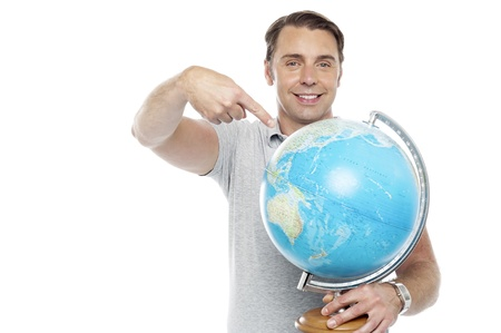 Man holding globe and pointing over it against white background photo