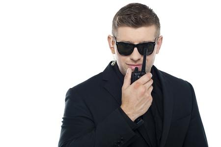 Smart young Sicherheitspersonal Kommunikation über das Walkie-Talkie auf weißem Hintergrund isoliert