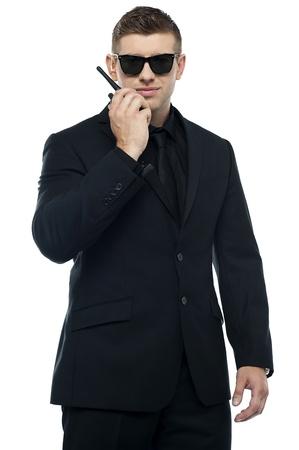 seguridad laboral: Joven oficial de seguridad sincero hablando a trav�s de su walkie-talkie aislado sobre fondo blanco. Medio retrato de la longitud