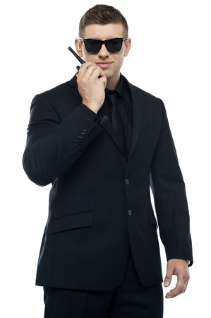 Young sincere security officer talking through his walkie-talkie isolated over white background. Half length portrait photo