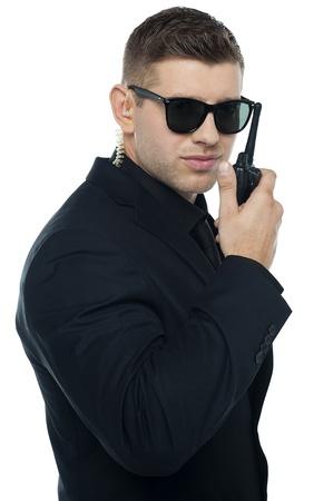 sicurezza sul lavoro: Chief Security Officer comunicando attraverso il suo walkie-talkie, isolato su sfondo bianco. Archivio Fotografico