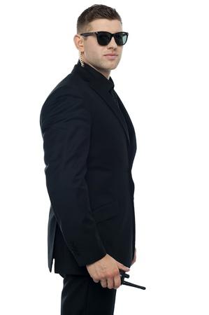 garde du corps: C�t� pose portrait de jeune agent de s�curit� et intelligent tenant talkie-walkie appareil en main Banque d'images