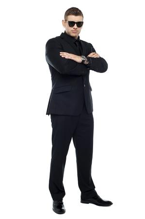 Junge stilvolle Türsteher in einem schwarzen Anzug mit verschränkten Armen und Tragen von Schutzbrillen