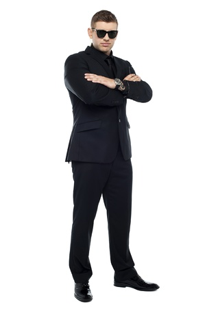 Young stylish bouncer in a black suit, arms folded and wearing goggles