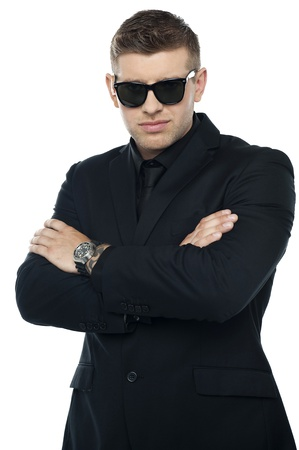 Young stylish bouncer in a black suit, arms folded. Half length portrait photo