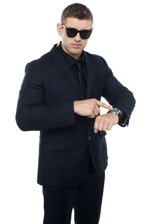 Security official pointing at his watch isolated against white background photo