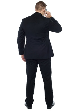 Back pose of young male security person holding earpiece and listening carefully photo
