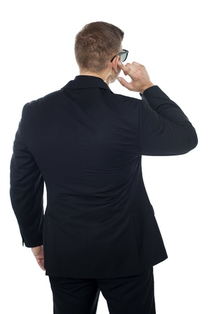 Bodyguard listening to vital information carefully while holding his earpiece. Back pose photo