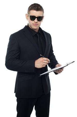vigilante de seguridad: Oficial de seguridad por escrito en el portapapeles mientras mira a usted