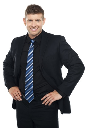 Confident young businessman posing casually. Hands on his waist