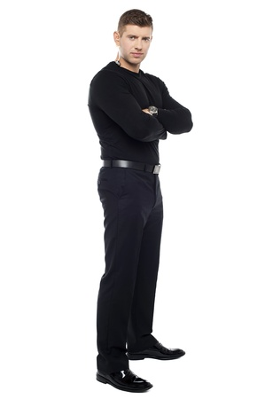 Handsome young bodyguard, full length portrait. Arms folded photo