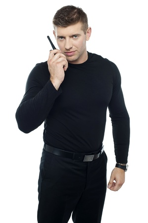 Bouncer guy communicating with his walkie-talkie isolated against white background photo