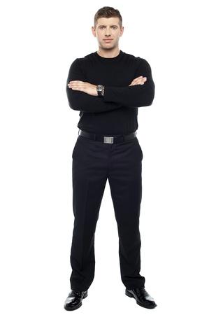 Junge intelligente Türsteher posiert mit verschränkten Armen auf weißem Hintergrund.
