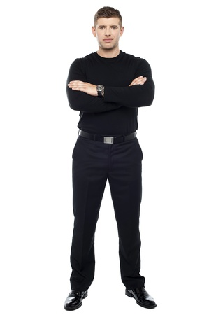 Young smart bouncer posing with his arms crossed isolated over white background. photo