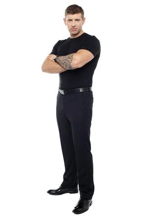 Bouncer met tattoo op de hand poseren met armen gekruist geïsoleerd tegen witte achtergrond