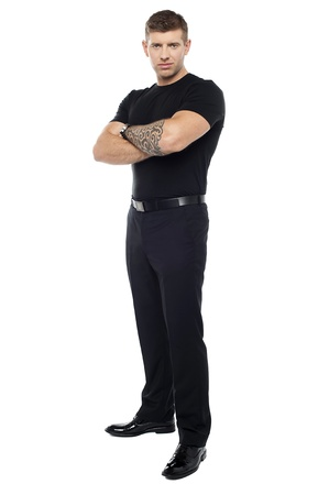 Bouncer with tattoo on hand posing with arms crossed isolated against white background