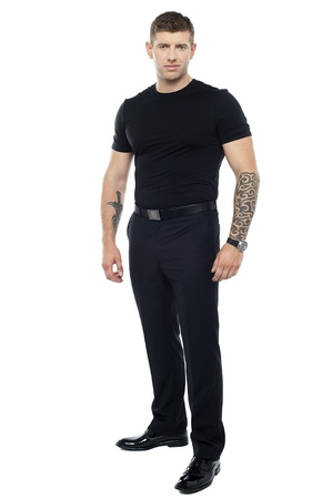 Strong male bouncer. Tattoo on both his hands. Full length shot Stock Photo