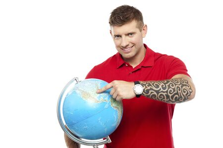 Smiling cool guy holding and pointing at the globe isolated against white photo