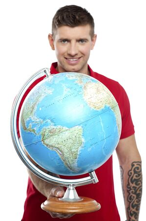 Guy with tattoos showing globe to camera isolated on white background photo