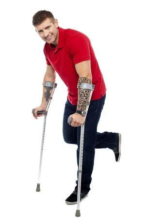 recovering: Young man recovering from severe accident. Walking with help of crutches and smiling Stock Photo