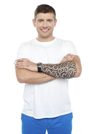 Picture of a young smiling masculine chap with huge tattoos drawn on his hand. Arms folded photo