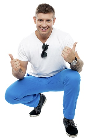 Cheerful young man showing double thumbs up in squatting position isolated against white background photo