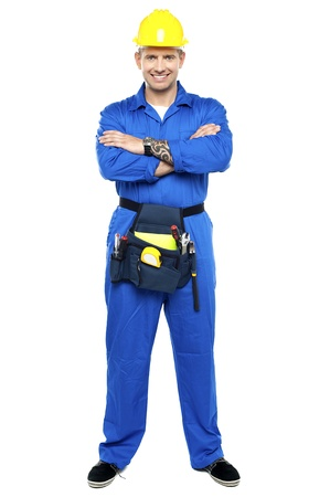 Confident young industrial contractor posing with folded arms photo