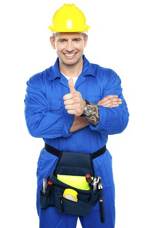 Smiling young industrial contractor showing thumbs up to camera Stock Photo - 15338513