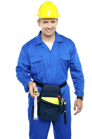 Smart smiling repairman with tools pouch tied to his waist holding measuring tape photo