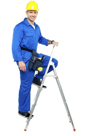Cheerful young construction worker climbing up the stepladder photo