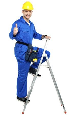 escaleras: Contratista Industrial se�alando los pulgares para arriba mientras que sube en la escalera Foto de archivo