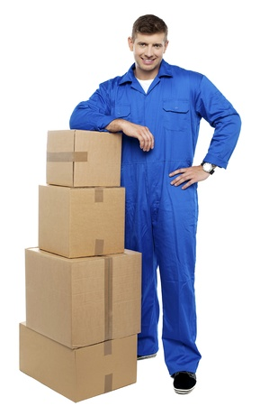 Relocation staff member in uniform resting against stack of cartons photo