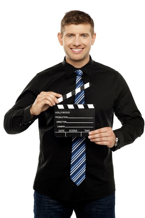 Young guy holding clapboard. Its showtime photo