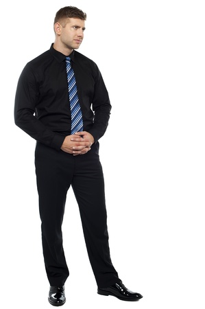Thoughtful serious businessman. Full length portrait photo