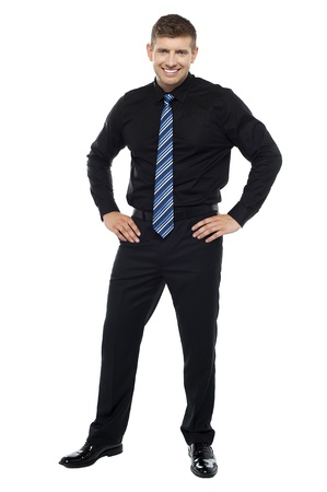 Casual portrait of handsome young businessman posing with hands on his waist photo