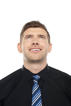 Smiling male executive looking upwards isolated over white background photo