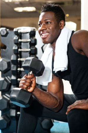 Young gym instructor toning his biceps, triceps and forearm while exercising with heavy dumbbell Stock Photo - 15441747