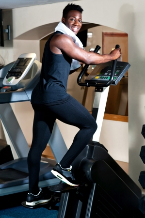 Young smiling fit african male burning calories in the gym on an elliptical photo