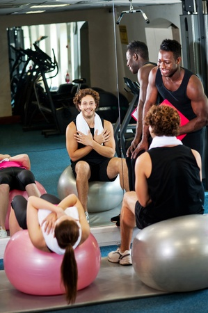 instructing: Trainer instructing gym clients on how to use exercise ball to effectiveness