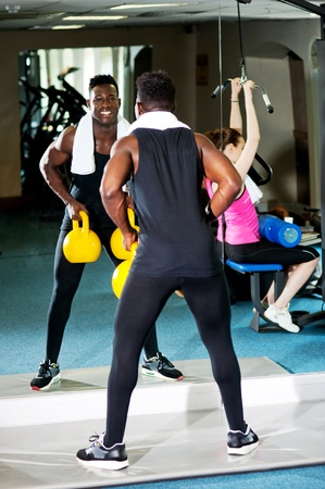 Its workout time  African male lifting heavy kettlebells while white female is working out in the multi gym Stock Photo - 15441744