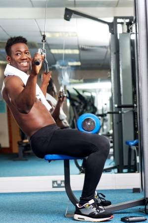 Fit african trainer working out in multi gym  Keeping fit and healthy photo