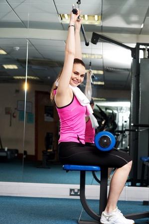 Woman toning her upper and core muscles in multi gym  Looking at camera Stock Photo - 15441743