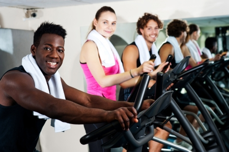 Energetic group working out together in a gym on elliptical photo