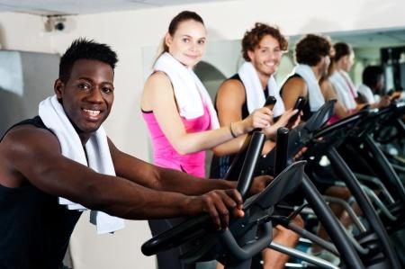 eliptica: Grupo energ�tico trabajando juntos en un gimnasio en el el�ptico
