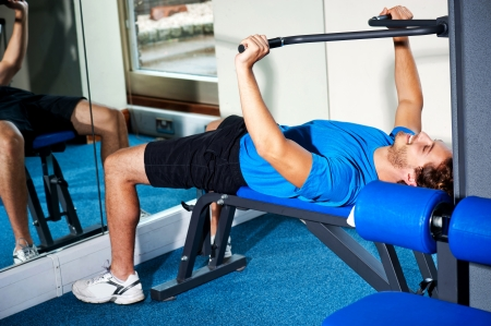 body toning: Fitness guy lying on bench and exercising, burning calories Stock Photo