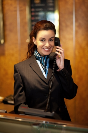receptionist: Stylish female attendant at hotel reception communicating on phone Stock Photo