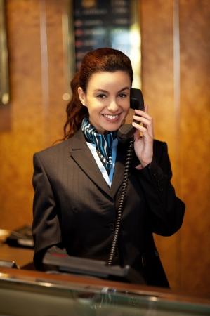 hotel reception: Stylish female attendant at hotel reception communicating on phone Stock Photo
